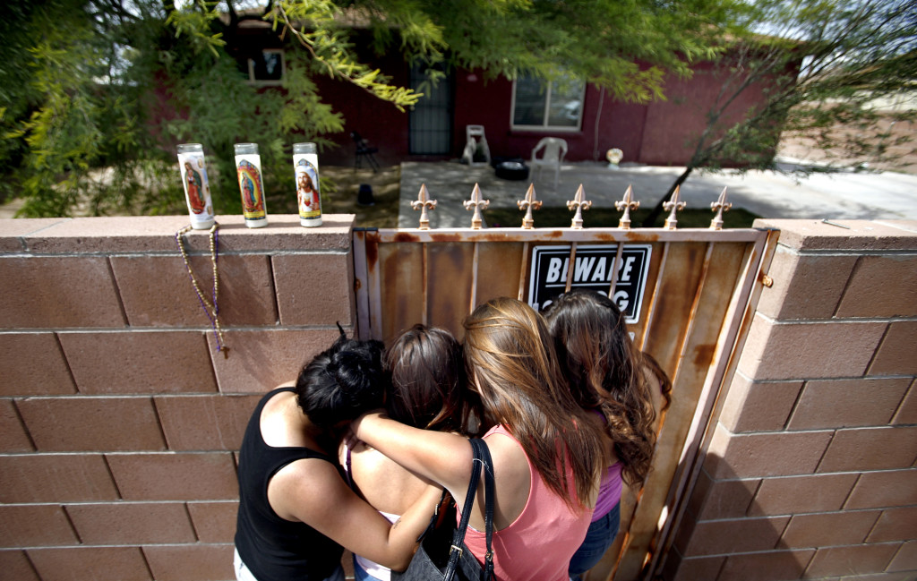 Friends of 17-year-old Isela Rodriguez hold each other outside the home in the 800 block of west Calle Medina where Rodriguez and four others were found dead Tuesday, after leaving a memorial candle, Wednesday, May 13, 2015, Tucson, Ariz. Kelly Presnell / Arizona Daily Star