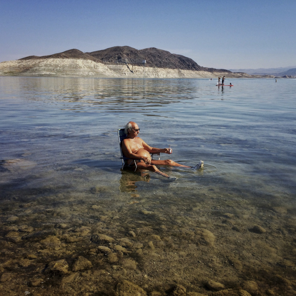 "Roger Dell relaxes in the water at Lake Mead's Boulder Beach, June 20, 2015. A high-water mark or ""bathtub ring"" is visible on the shoreline; Lake Mead is down over 150 vertical feet."