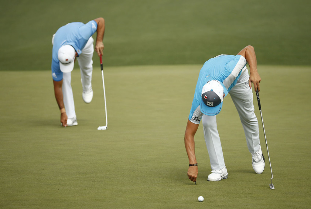Apr 10, 2015; Augusta, GA, USA; Rickie Fowler (right) and Jason Day (left) repair their ball marks on the 2nd green during the second round of The Masters golf tournament at Augusta National Golf Club. Mandatory Credit: Rob Schumacher-USA TODAY Sports