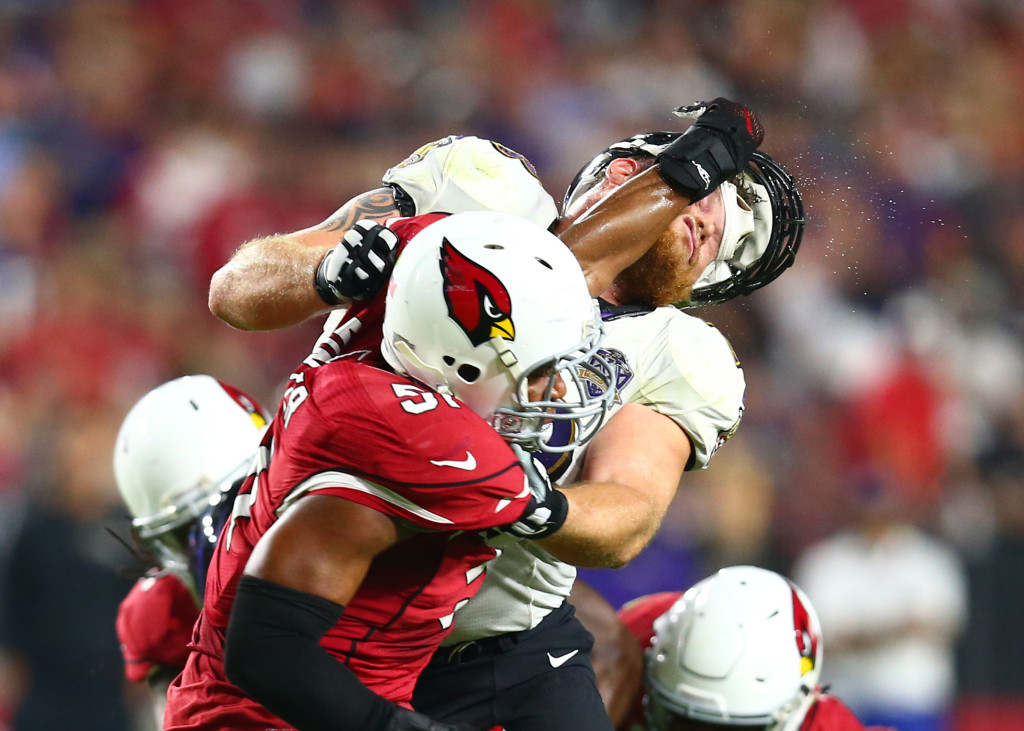 Oct 26, 2015; Glendale, AZ, USA; Baltimore Ravens guard Marshal Yanda (right) loses his helmet as he blocks Arizona Cardinals linebacker Kevin Minter in the second quarter at University of Phoenix Stadium. Mandatory Credit: Mark J. Rebilas-USA TODAY Sports