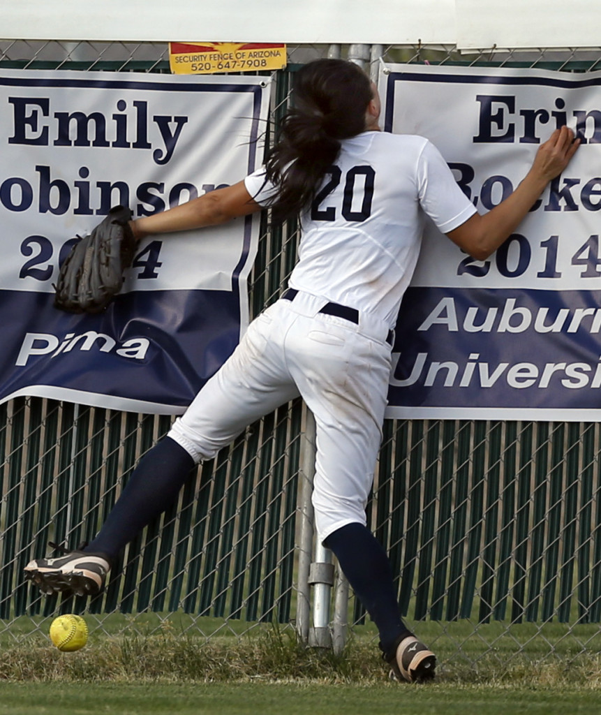 Ironwood Ridge's Merrilee Miller (20) slams head first into the centerfield fence chasing a fly ball by Canyon del Oro's Ellessa Bonstrom (10) that ended up a triple in the third inning of their game at Ironwood Ridge High School, Tuesday, April 14, 2015, Tucson, Ariz. Kelly Presnell / Arizona Daily Star