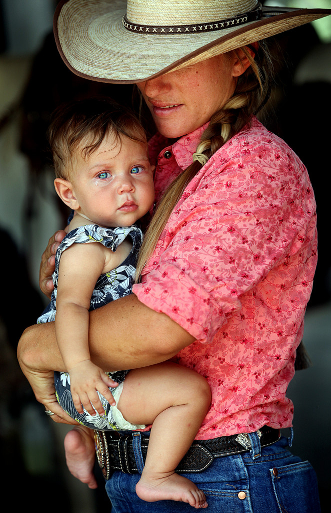 MARK.LEVY@SVHERALD.COM c08.mjl.cowgirlmom.jpg Samantha Jepson holds her 7-month-old daughter, Mina Soriano, Tuesday while at the J-Six Ranch Equestrian Center in Benson where she is a horse trainer. Jepson won the Arizona Horseman's Challenge in April. She has been ranching all of her life.