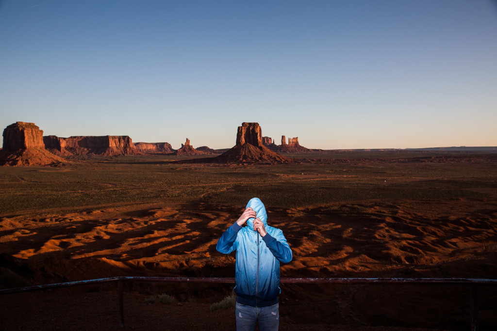 4/9/2015 - Vlad Odobescu prepares to unzip his hoodie after posing for a portrait in the extreme morning cold of Monument Valley Thursday morning in Northern Ariz.. Photo by Deanna Dent/Cronkite Journal