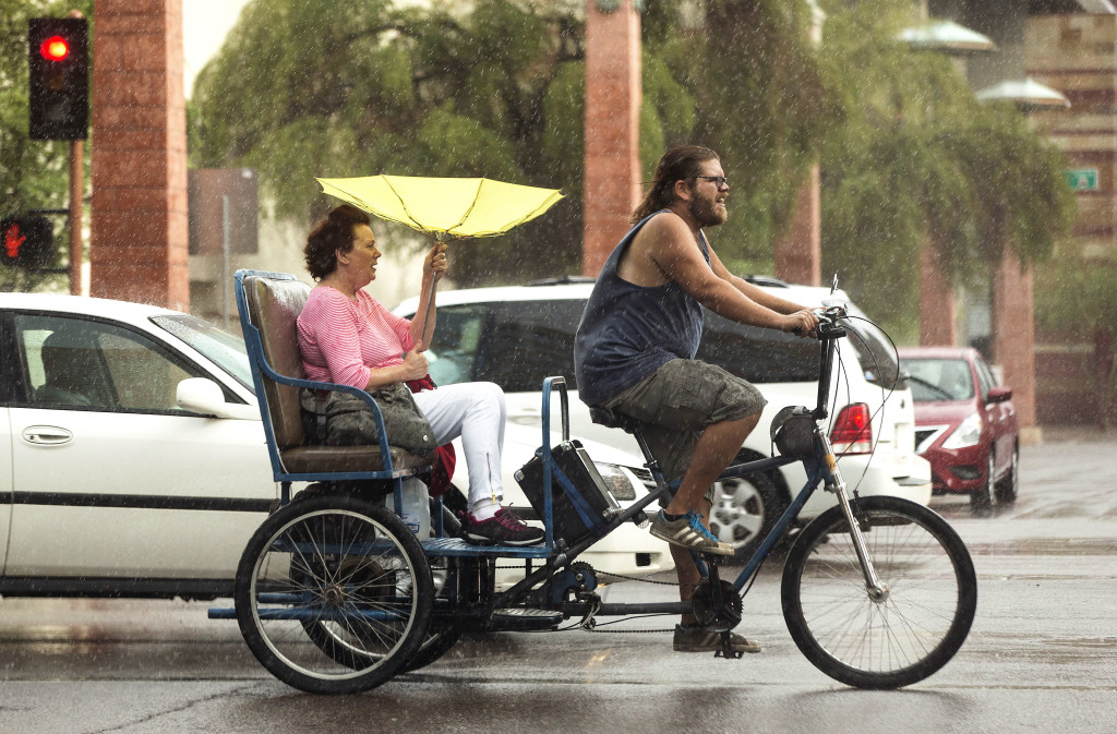 A Pedicab drives down Van Buren Road carrying a woman with a yellow umbrella in the rain on Friday, June 5, 2015 in Phoenix, AZ.