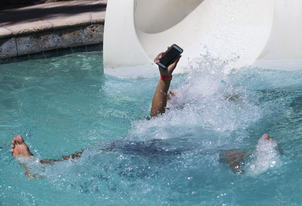 Alex Reyes, 18 from Chandler, keeps his cell phone from going underwater while using the slide at the River Ranch at Pointe Hilton Squaw Peak April 19, 2015.