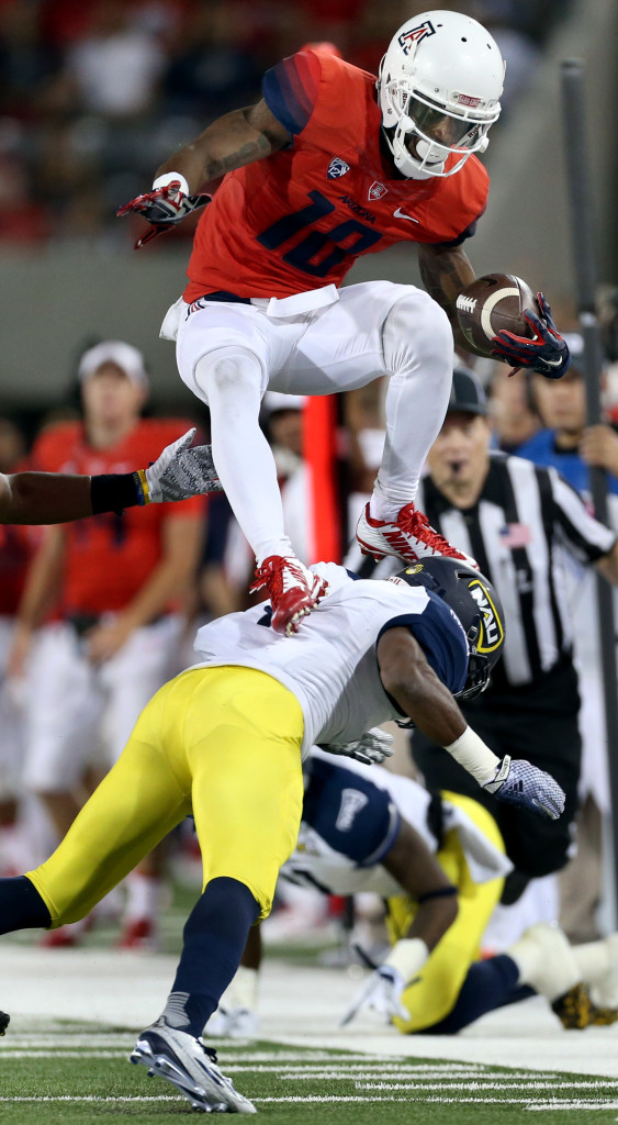 Arizona wide receiver Samajie Grant (10) uses Northern Arizona safety LeAndre Vaughn (4) as step while hurdling over defenders to pick up extra yards after a sideline catch in the second quarter of their game at Arizona Stadium, Saturday Sept. 19, 2015, Tucson, Ariz.  Kelly Presnell / Arizona Daily Star